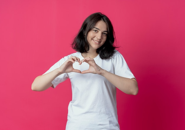Smiling young pretty caucasian girl doing heart sign at camera isolated on crimson background with copy space