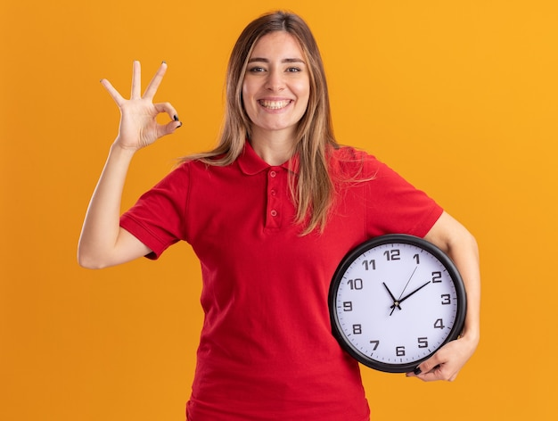 Sorridente giovane ragazza abbastanza caucasica gesti il segno giusto della mano e tiene l'orologio sull'arancia