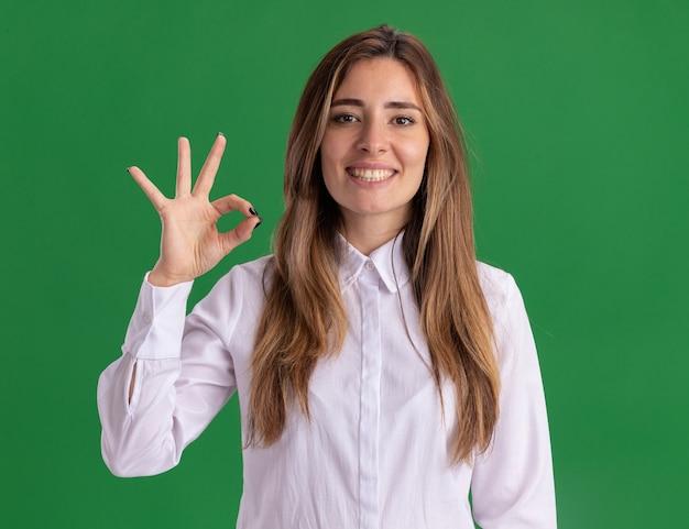 Улыбающаяся молодая симпатичная кавказская девушка жестикулирует знак рукой на зеленом