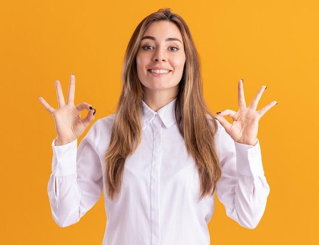 Sorridente giovane ragazza abbastanza caucasica gesti il segno giusto della mano con due mani sull'arancia