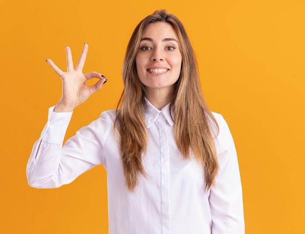 La giovane ragazza abbastanza caucasica sorridente fa un gesto ok con la mano