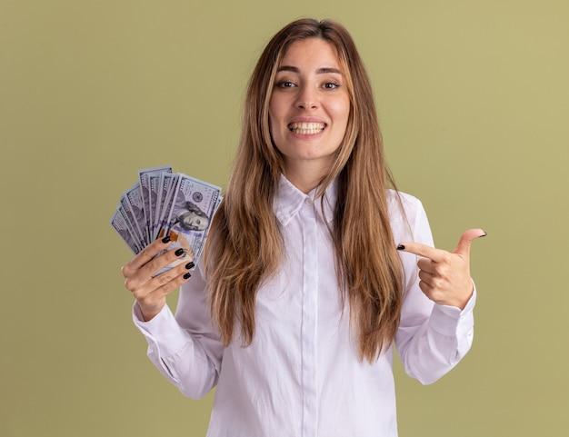 웃고 있는 젊고 예쁜 백인 소녀는 복사 공간이 있는 올리브 녹색 벽에 격리된 돈을 들고 가리키고 있습니다.