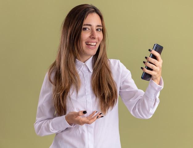 Улыбающаяся молодая симпатичная кавказская девушка держит и указывает рукой на телефон