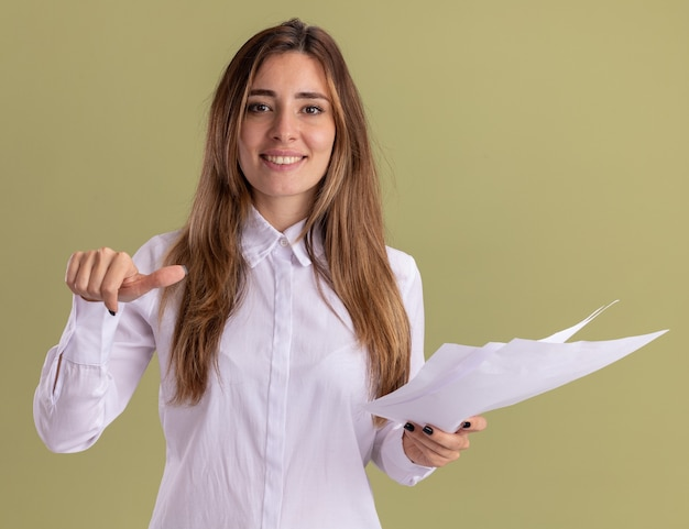 Smiling young pretty caucasian girl holds blank paper sheets and points at side isolated on olive green wall with copy space