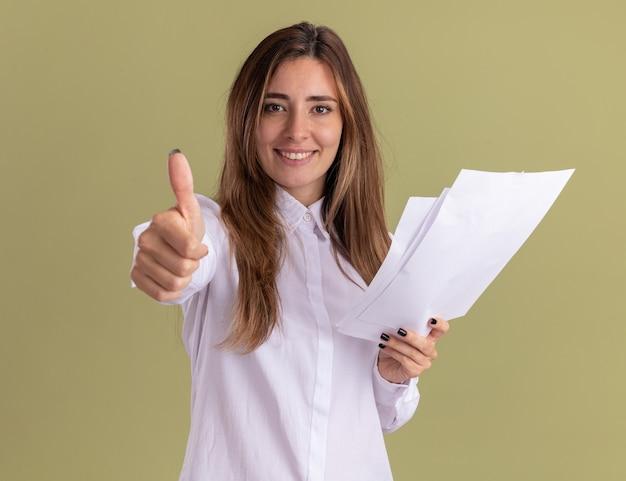 La giovane ragazza abbastanza caucasica sorridente tiene i fogli di carta in bianco ed i pollici su isolati sulla parete verde oliva con lo spazio della copia