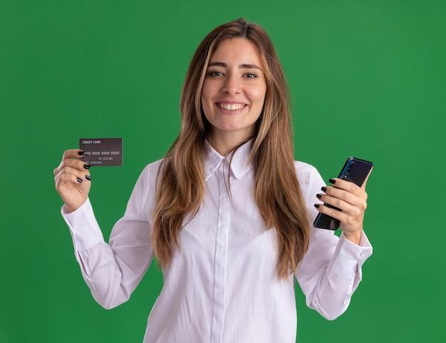 웃는 젊은 예쁜 백인 여자 그린에 신용 카드와 전화를 보유