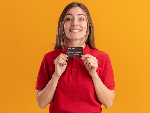 Smiling young pretty caucasian girl holds credit card on orange