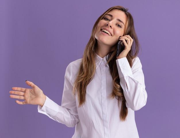 Улыбающаяся молодая симпатичная кавказская девушка держит руку открытой и разговаривает по телефону на фиолетовой стене с копией пространства