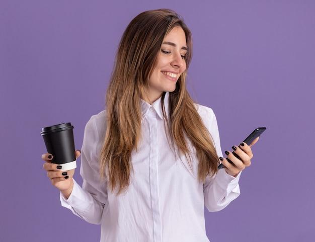 웃는 젊은 예쁜 백인 여자 종이 컵을 보유하고 보라색에 전화를 찾습니다