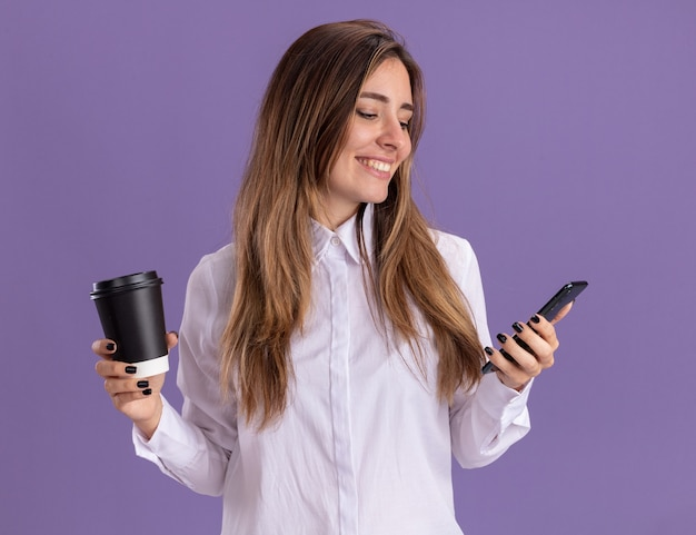 La giovane ragazza abbastanza caucasica sorridente tiene il bicchiere di carta e guarda il telefono sulla porpora Foto Gratuite