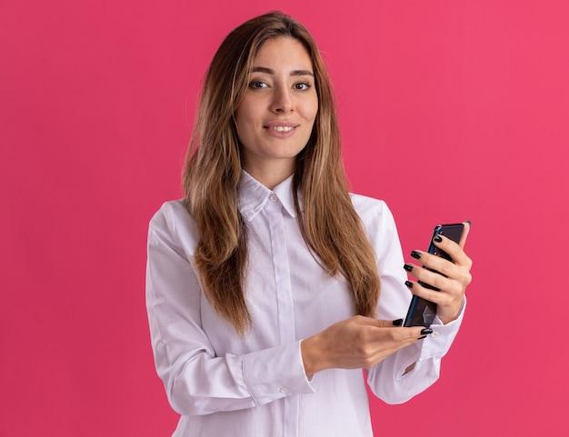 笑顔の若いかなり白人の女の子が電話を持ってピンクのカメラを見る