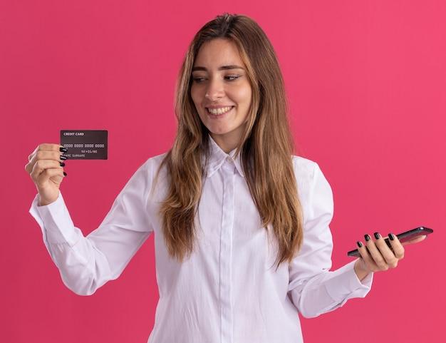 La giovane ragazza abbastanza caucasica sorridente tiene il telefono ed esamina la carta di credito isolata sulla parete rosa con lo spazio della copia