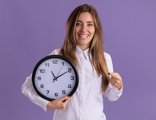 La giovane ragazza abbastanza caucasica sorridente tiene e indica l'orologio sulla porpora