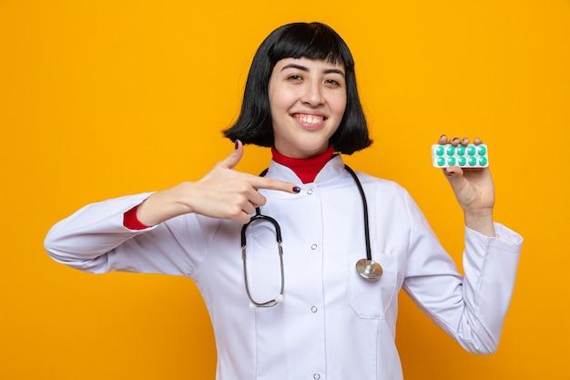 Улыбающаяся молодая симпатичная кавказская девушка в униформе врача со стетоскопом, держащая и указывающая на упаковку таблеток