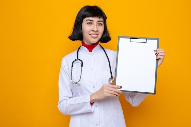 クリップボードを保持している聴診器で医者の制服を着た若いかなり白人の女の子の笑顔