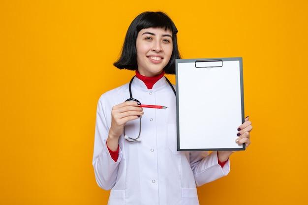ペンとクリップボードを保持している聴診器で医者の制服を着た若いかなり白人の女の子の笑顔