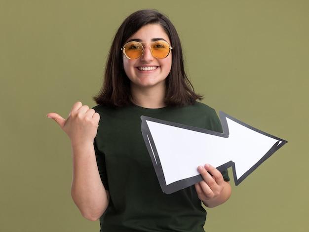 Улыбающаяся молодая симпатичная кавказская девушка в солнцезащитных очках держит стрелку и указывает в сторону на оливково-зеленом
