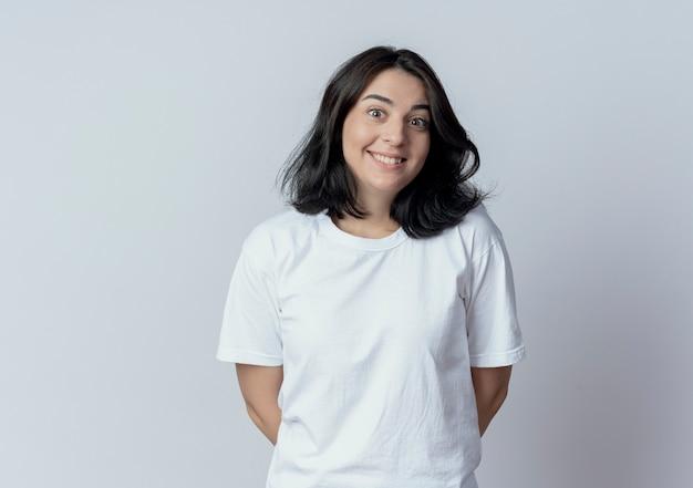 Sorridente giovane ragazza abbastanza caucasica mantenendo le mani dietro la schiena isolato su sfondo bianco con spazio di copia