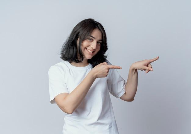 Улыбающаяся молодая симпатичная кавказская девушка смотрит в камеру и указывает на сторону, изолированную на белом фоне
