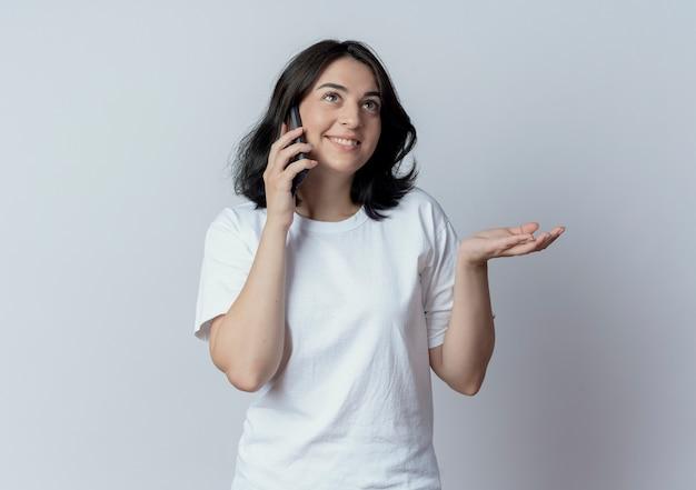 Sorridente giovane ragazza abbastanza caucasica alzando lo sguardo parlando al telefono e mostrando la mano vuota isolata su sfondo bianco con spazio di copia