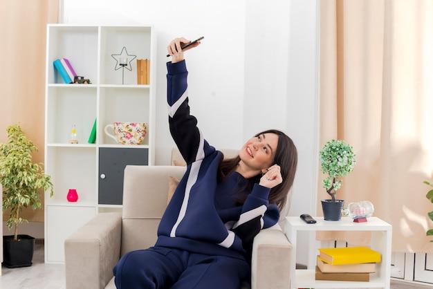 Sorridente giovane bella ragazza caucasica seduto sulla poltrona nel soggiorno progettato prendendo selfie e tenendo la mano in aria