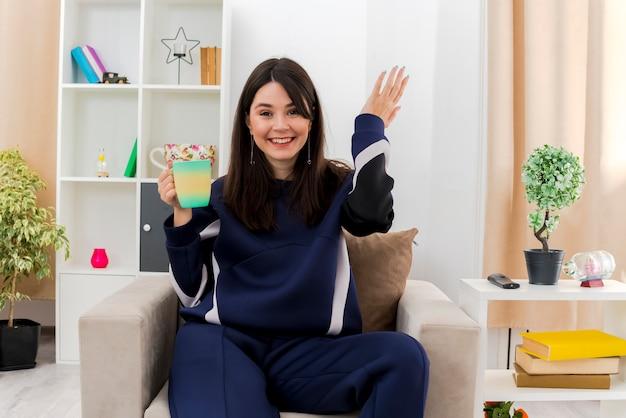 空気中に手を保つカップを保持している設計されたリビングルームの肘掛け椅子に座っている若いかわいい白人の女の子