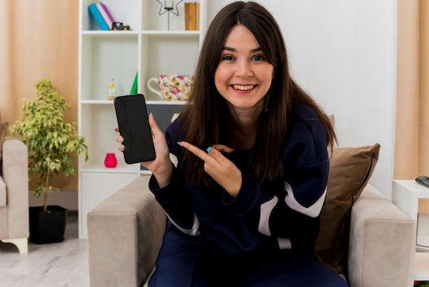 Улыбающаяся молодая симпатичная кавказская девушка сидит на кресле в дизайнерской гостиной, показывая мобильный телефон, указывая на нее и