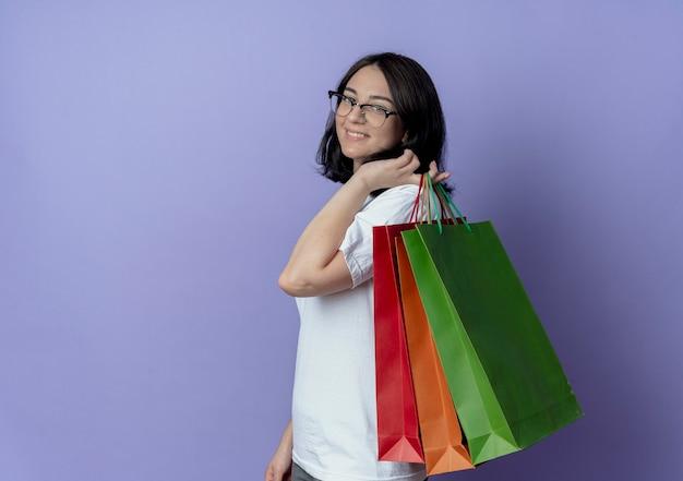 Улыбающаяся молодая симпатичная кавказская девушка, стоящая в профиле, держит сумки на плече, изолированные на фиолетовом фоне с копией пространства