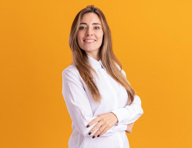 웃는 젊은 예쁜 백인 여자 복사 공간 오렌지 벽에 고립 된 교차 팔 스탠드