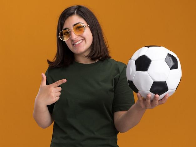 Sorridente giovane bella ragazza caucasica con gli occhiali da sole che tiene e indica la palla