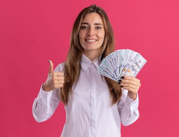 Улыбающаяся молодая симпатичная кавказская девушка показывает палец вверх и держит деньги на розовом
