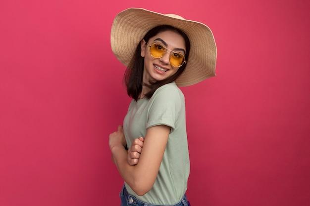 コピースペースとピンクの壁に分離された縦断ビューで閉じた姿勢で立っているビーチ帽子とサングラスを身に着けている若いかわいい白人の女の子の笑顔