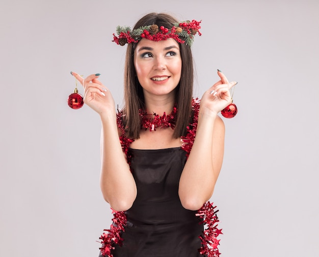 白い背景で隔離の側を見てクリスマスつまらないものを保持している首の周りにクリスマスの頭の花輪と見掛け倒しの花輪を身に着けている若いかわいい白人の女の子の笑顔