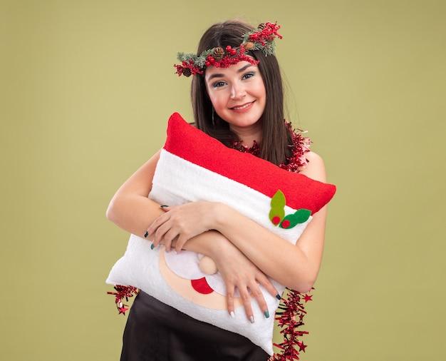 Улыбающаяся молодая симпатичная кавказская девушка в рождественском венке и гирлянде из мишуры на шее держит подушку санта-клауса, глядя в камеру, изолированную на оливково-зеленом фоне с копией пространства
