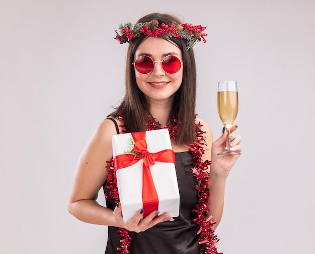 白い背景で隔離のカメラを見てシャンパンとギフトパッケージのガラスを保持しているメガネと首の周りにクリスマスのヘッドリースと見掛け倒しの花輪を身に着けている若いかわいい白人の女の子を笑顔