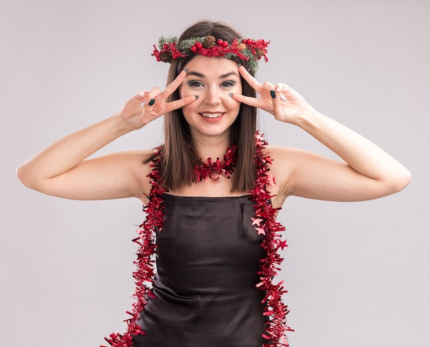 Smiling young pretty caucasian girl wearing christmas head wreath and tinsel garland around neck looking at camera showing v-sign symbols near eyes isolated on white background