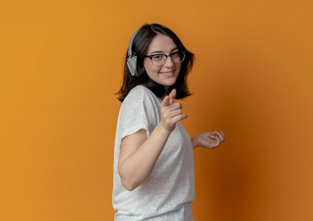 眼鏡とヘッドフォンを身に着けている笑顔の若いかなり白人の女の子が空中に手を保ち、コピースペースでオレンジ色の背景に分離されたカメラを指して縦断ビューに立っています
