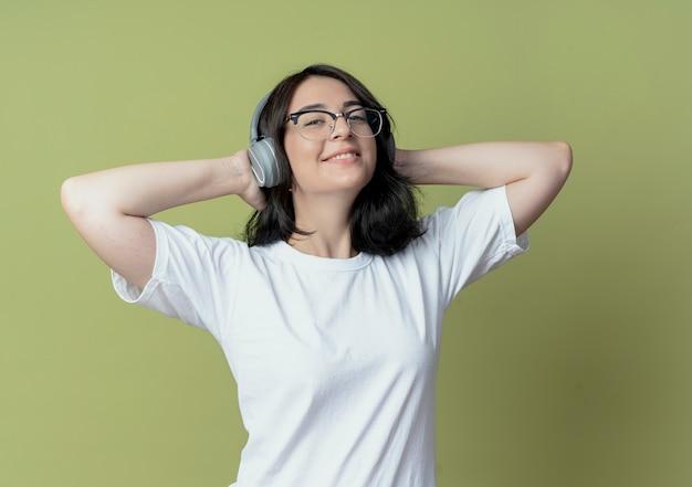 Sorridente giovane ragazza abbastanza caucasica con gli occhiali e le cuffie ascoltando musica e tenendo le mani dietro la testa isolata su sfondo verde oliva