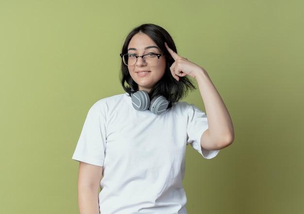 Sorridente giovane ragazza abbastanza caucasica con gli occhiali e le cuffie sul collo mettendo il dito sul tempio isolato su sfondo verde oliva con lo spazio della copia