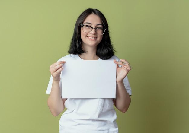 Sorridente giovane ragazza piuttosto caucasica con gli occhiali in possesso di carta isolato su sfondo verde oliva con spazio di copia
