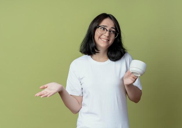 컵을 들고 측면을보고 올리브 녹색 배경에 고립 된 빈 손을 보여주는 안경을 쓰고 웃는 젊은 예쁜 백인 여자