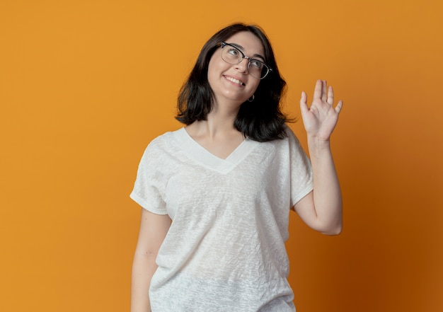 Smiling young pretty caucasian girl wearing glasses looking up and gesturing hi isolated on orange background with copy space