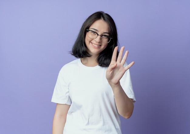 コピースペースで紫色の背景に分離された手で4を示す眼鏡をかけている若いかなり白人の女の子の笑顔