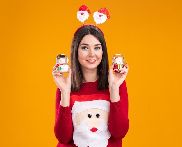 Улыбающаяся молодая симпатичная кавказская девушка в головной повязке и свитере санта-клауса держит снеговика и фигурки санта-клауса, глядя в камеру, изолированную на оранжевом фоне с копией пространства