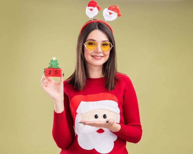 サンタクロースのセーターとヘッドバンドを身に着けている若いかわいい白人の女の子を笑顔で保持し、日付とクリスマスツリーのおもちゃを指しています 無料写真
