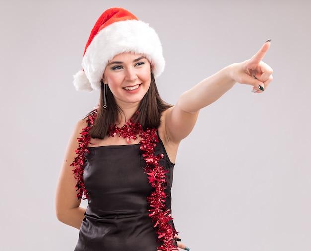Улыбающаяся молодая симпатичная кавказская девушка в новогодней шапке и мишурной гирлянде на шее, указывая и глядя в сторону, держа руку за спиной, изолированную на белом фоне