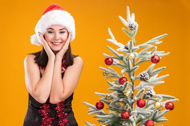 오렌지 배경에 고립 된 카메라를보고 얼굴에 손을 유지 장식 된 크리스마스 트리 근처에 서있는 목 주위에 산타 모자와 반짝이 갈 랜드를 입고 웃는 젊은 예쁜 백인 여자