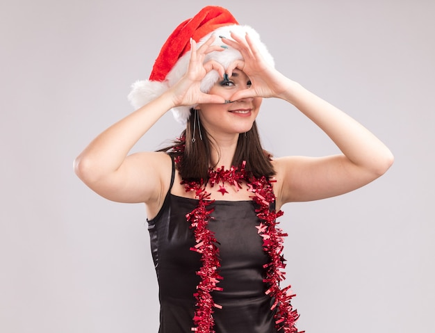 Smiling young pretty caucasian girl wearing santa hat and tinsel garland around neck looking at camera doing heart sign in front of eye isolated on white background