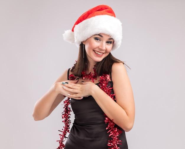 Sorridente giovane bella ragazza caucasica che indossa cappello da babbo natale e ghirlanda di orpelli intorno al collo guardando la telecamera tenendo le mani insieme sul petto isolato su sfondo bianco con spazio di copia