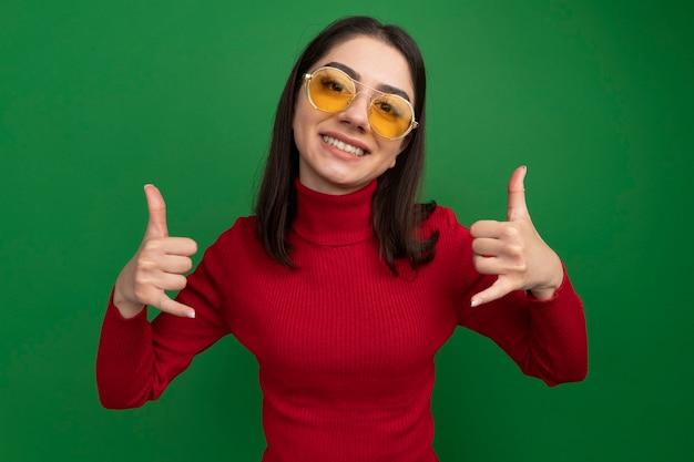 Улыбающаяся молодая симпатичная кавказская девушка в солнцезащитных очках делает свободный жест изолированной на зеленой стене